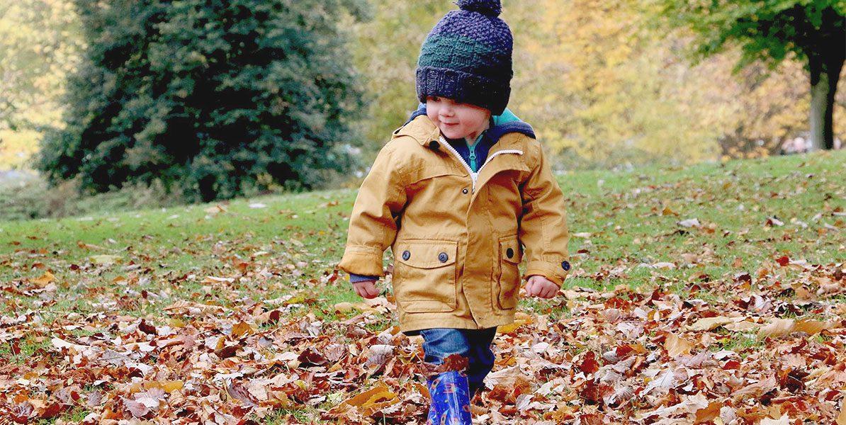 Kleinkind mit Mütze im Laub