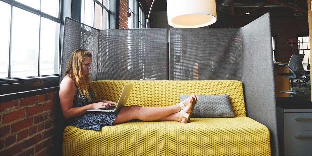Frau mit Laptop auf Couch im Büro